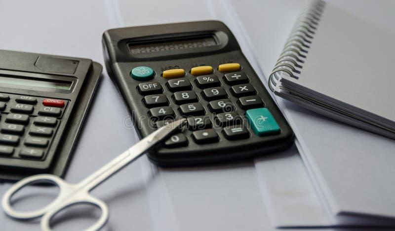 Calculadoras, tesouras, cadernos na tabela foto de stock