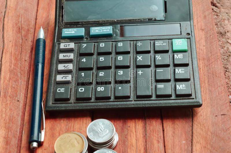 Calculate and ballpen on wooden table. Money, coins, calculator on the table. Concept calculation of the family budget, chart, accounting, rich, planning royalty free stock images