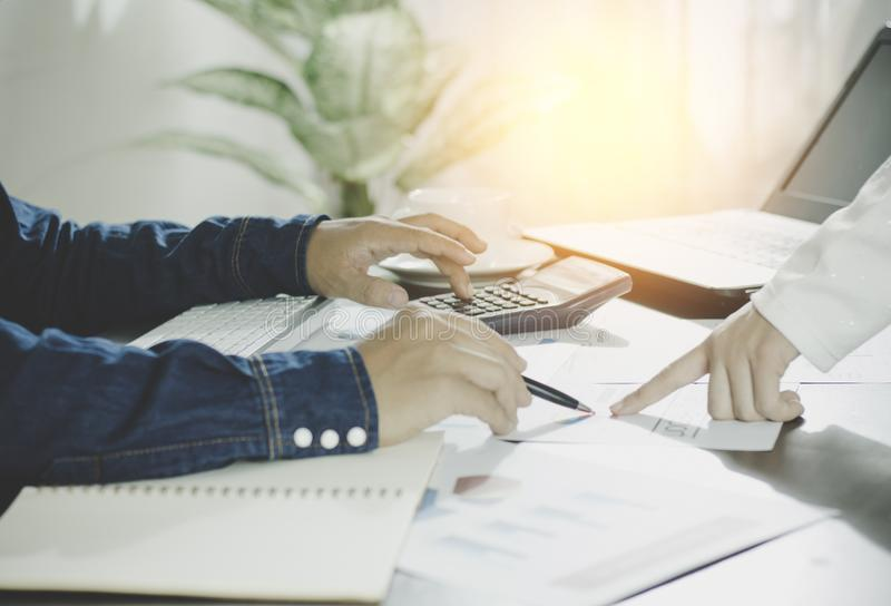 Calculate budget and business planning concept, two people couting revenue and expenditure by using calculator and looking paper royalty free stock photos