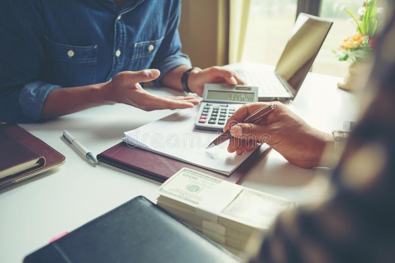 Calculate budget and business planning concept, two people couting revenue and expenditure by using calculator and looking paper royalty free stock image