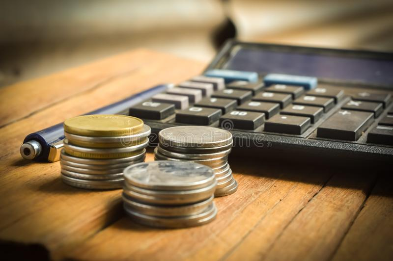 Calculate and coins  ballpen. Coins and calculate and other items on table,top view of Businessan, accounting, analysis, profit, planning, saving, banking stock photo