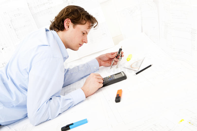 Calculating. Industrial design engineer calculating measurements and tolerances on a technical drawing using a calculator stock photos