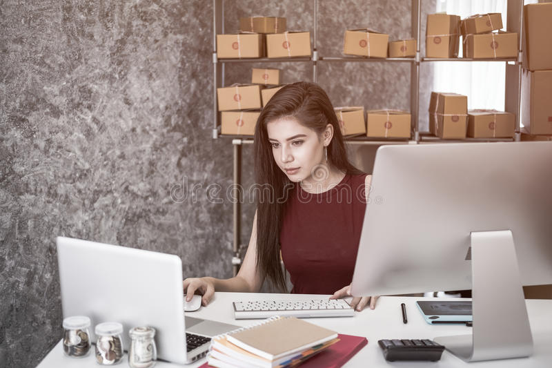 Calculating the cost of postage of a small package,. Small business enterprise concerns for online Shopping stock photography