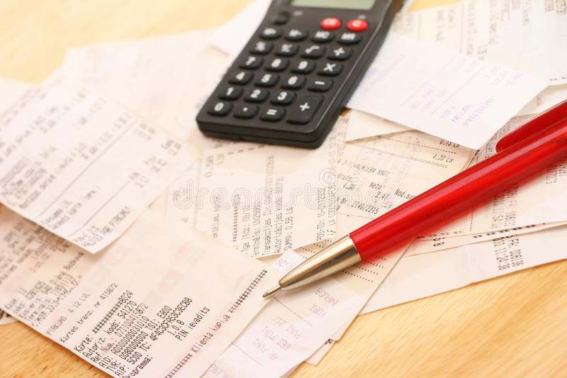 Calculating expenses. Cash checks, calculator and pen on the table royalty free stock images