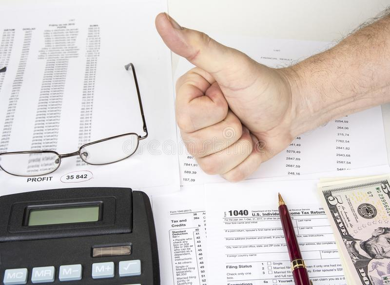 Calculating numbers for income tax return with pen, glasses and calculator. royalty free stock image