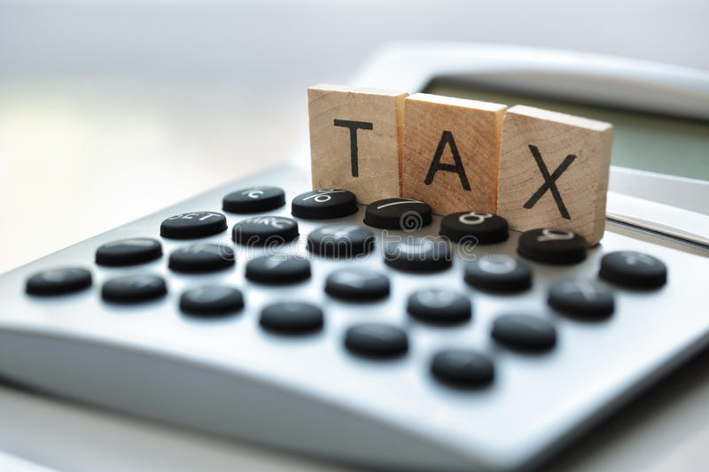 Calculating tax. Calculator with the word tax written in wooden block letters stock photography