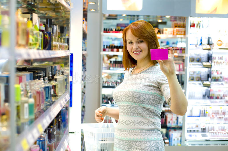 Calculation for purchases by a credit card. Young girl in shop of cosmetics holds a credit card in hand royalty free stock photo