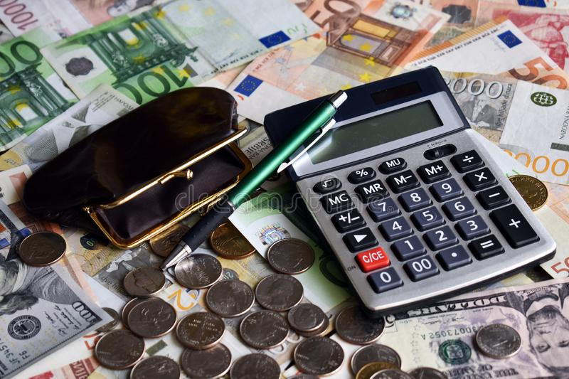 Calculator, ballpen, wallet and few coins on the lot of paper money royalty free stock photography