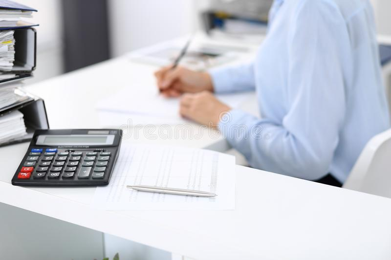 Calculator and binders with papers are waiting to be processed by business woman or bookkeeper back in blur. Internal. Audit and tax concept stock photo
