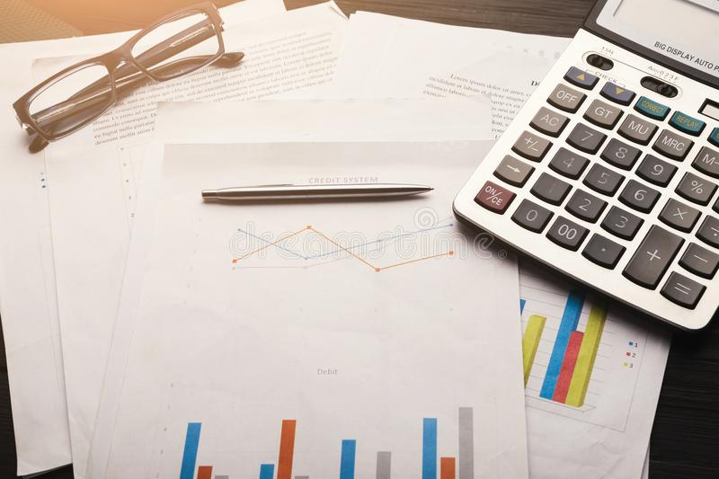 Calculator and business charts with credit system. Glasses, calculator and business charts with credit system, information and report background for financial stock images