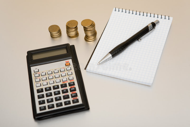 Calculator and coins. On table stock photos