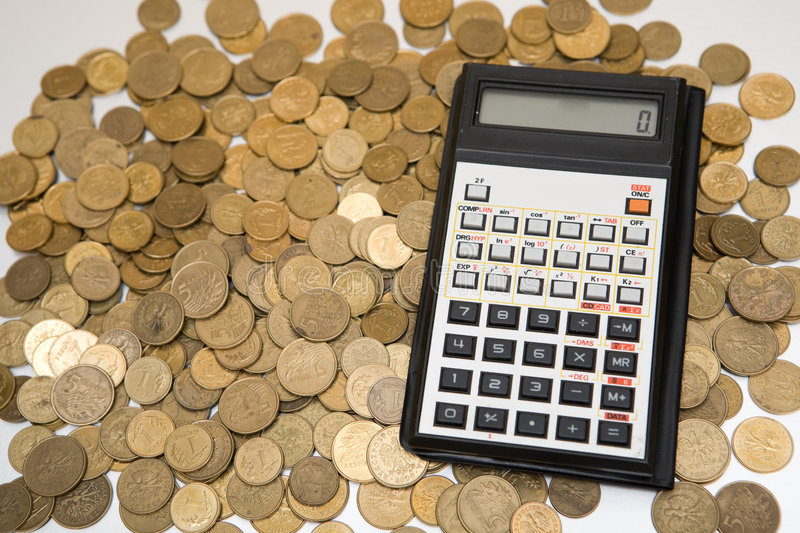 Calculator and coins. On table stock image