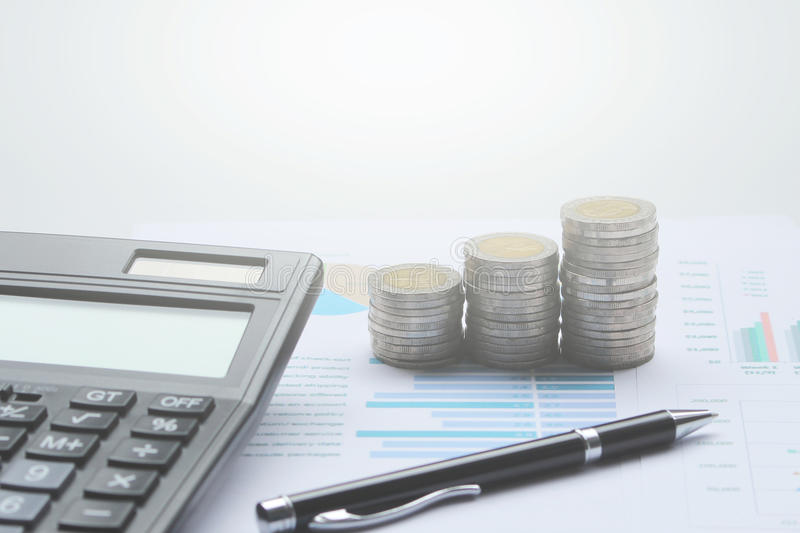 Calculator and Coins of thailand on the office desk investment a stock photos