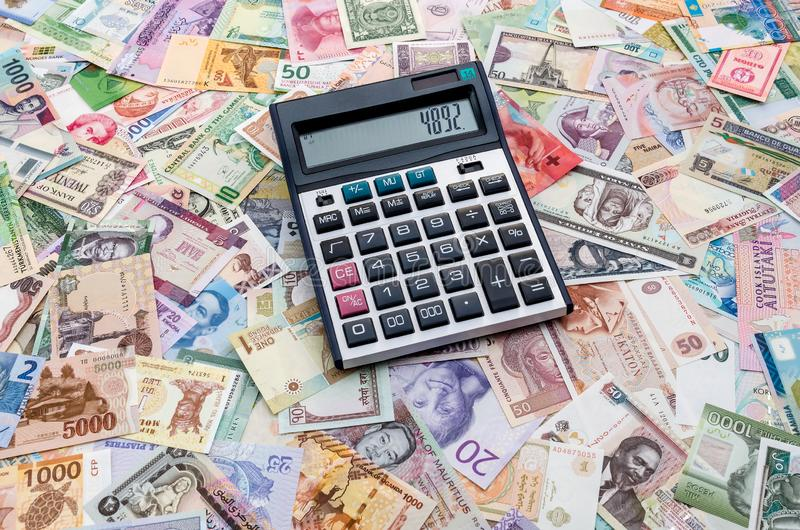 Calculator on collection of different countries banknotes royalty free stock photography