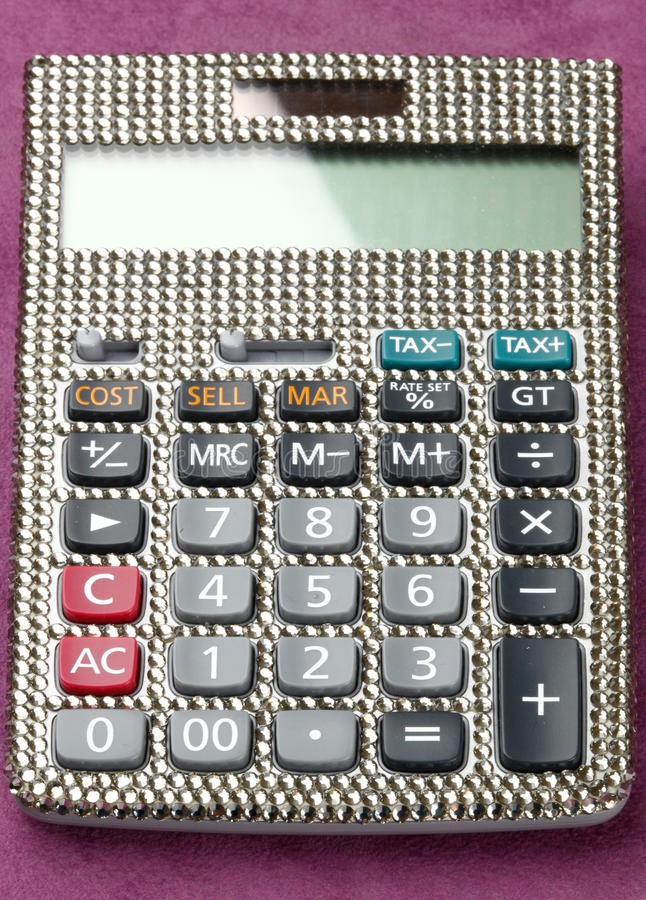 Calculator covered with swarovski crystals. On table of velvet royalty free stock image