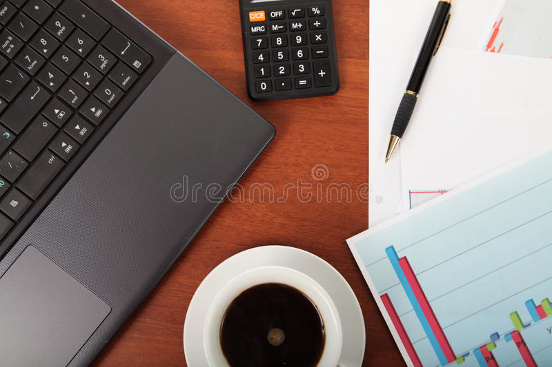 Calculator and cup of coffee on the financial documents. Calculator,laptop and cup of coffee on the financial documents on the table stock photography