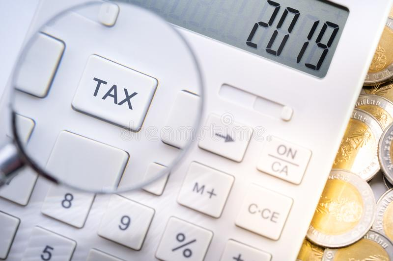 Calculator display number 2019 and magnifying glass zoom in tax button. On table with gold coins for business and taxation concept royalty free stock photo