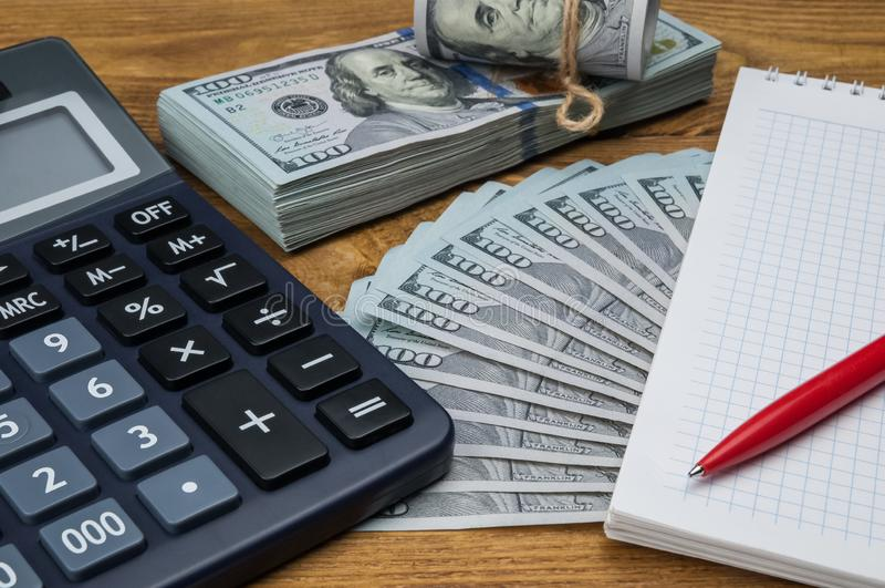 A calculator, dollars in a bundle, a roll and a fan, a notebook and a pen on a wooden textured table. royalty free stock image