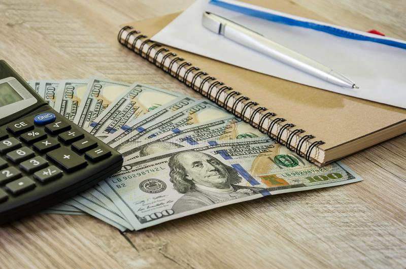 Calculator, dollars notepad on a wooden background, close-up stock photo