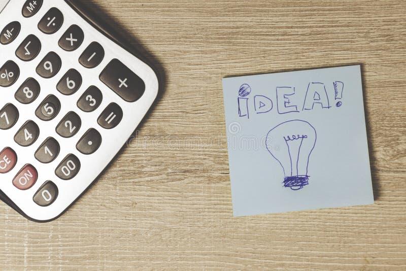 Calculator en blauwe post-it op het bureau stock afbeelding