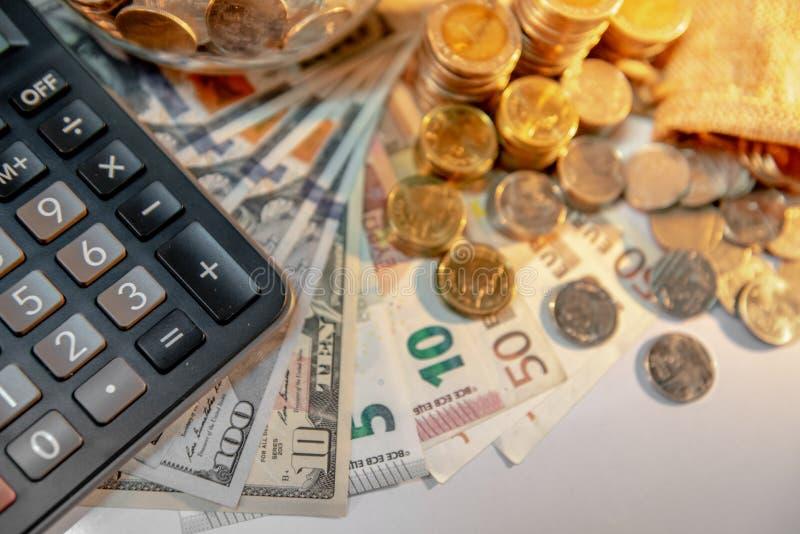 Calculator en internationale munt op de lijst stock afbeelding