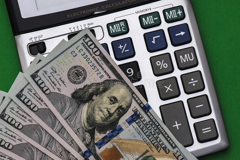 Calculator en munt op een groene achtergrond royalty-vrije stock fotografie