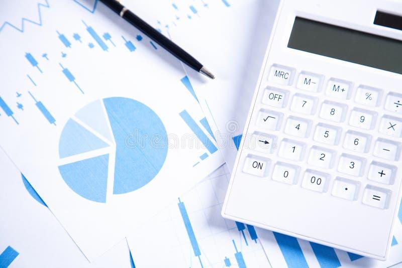 Calculator en pen met financiële grafieken royalty-vrije stock fotografie