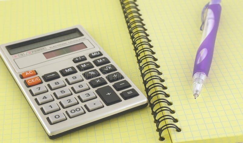 Calculator en pen op het schrijven-boek royalty-vrije stock afbeeldingen