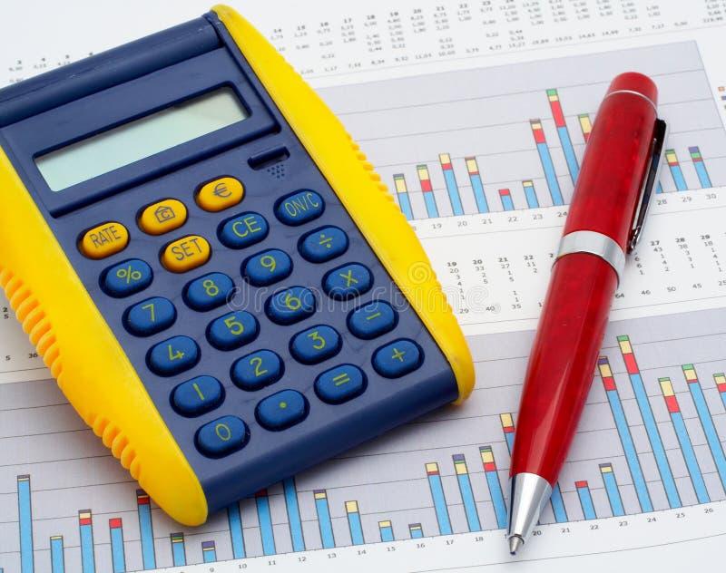 Calculator en pen op inkomensgrafiek stock foto