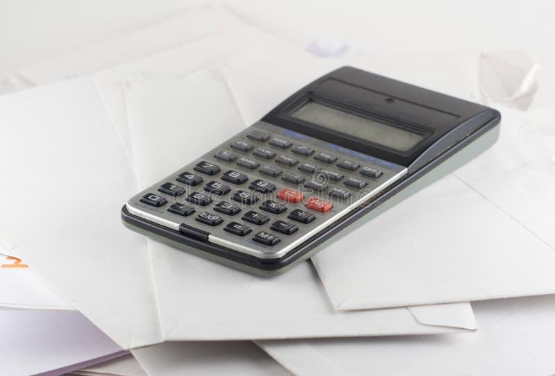 Calculator en rekeningenenveloppen stock afbeelding
