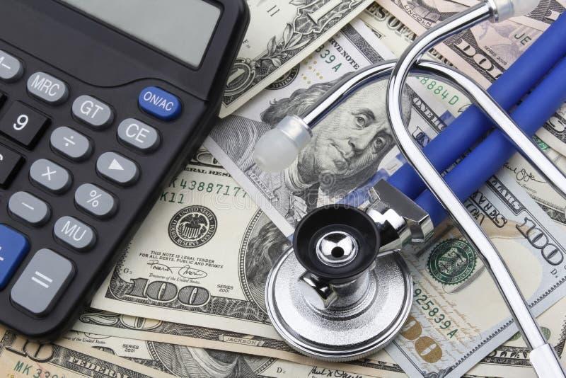 Calculator en Stethoscoop bovenop Amerikaanse dollar (USD) bankbiljetten stock foto