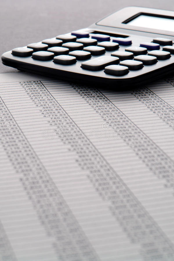 Calculator on Financial Spreadsheet with Numbers. Calculator on financial spreadsheet with columns of numbers and dollar figures for budget accounting and stock photo