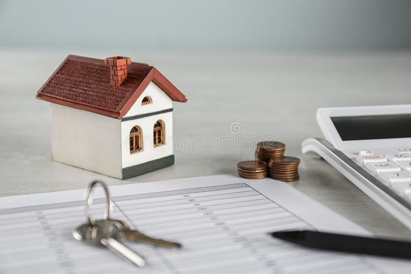 Calculator, house model, keys and documents. Real estate agent`s workplace stock photos