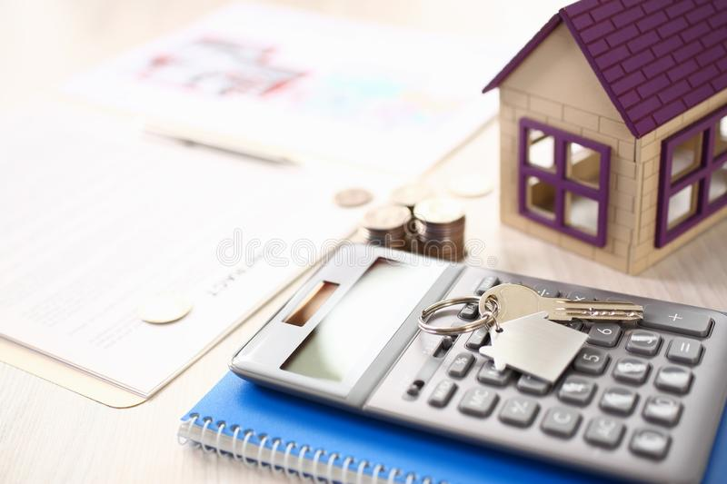 Calculator, House Model, Notebook, Key on Table stock photos