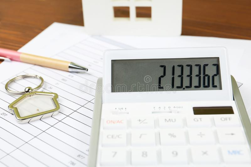Calculator, house shaped trinket, pen and documents. Real estate agent`s workplace royalty free stock image
