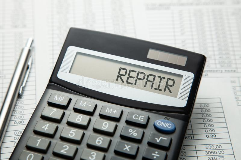 Calculator with the inscription on the REPAIR display on the paper tables. Home or car repair.  royalty free stock photos