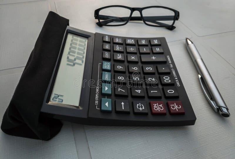 Calculator met een paar van glazen en een pen stock afbeeldingen