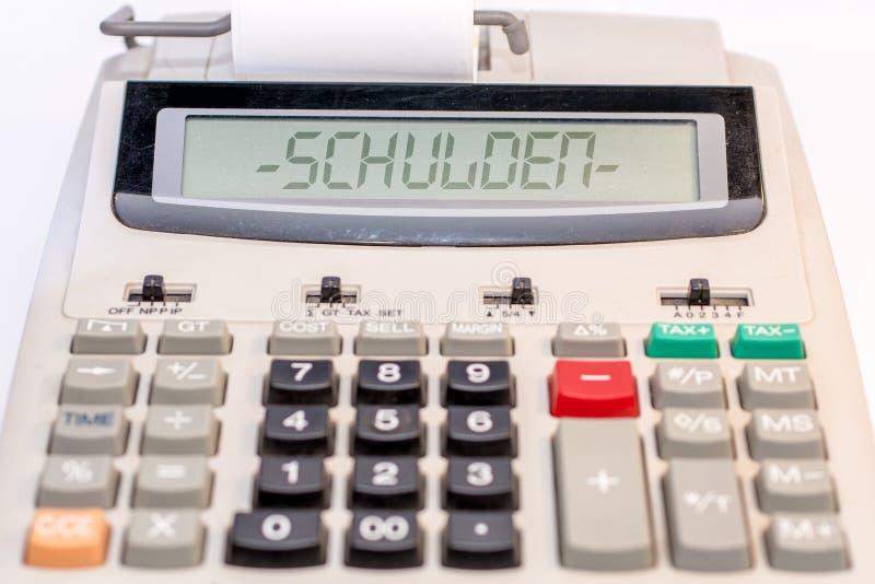 Calculator met het duitse woord 'schulden' in het display stock afbeeldingen