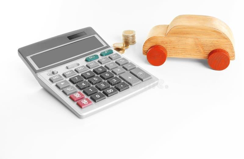 Calculator met muntstukken en stuk speelgoed op witte achtergrond stock afbeelding