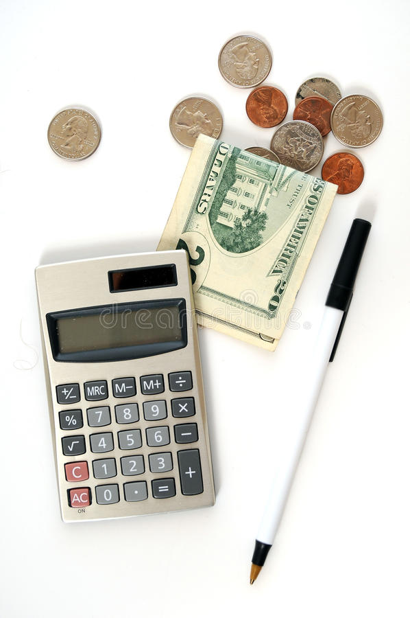Calculator with Money and Coins. Calculator with a twenty dollar bill and a bunch of coins and a pen on a white table. This image demonstrates taxes, accountants royalty free stock image