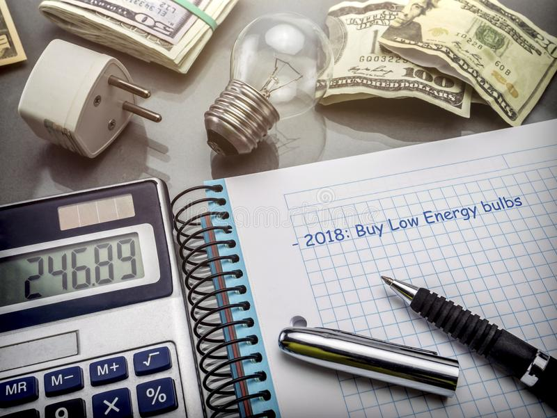 Calculator and money next to a light bulb, writing in agenda year 2018 to buy bulbs of low consumption royalty free stock images