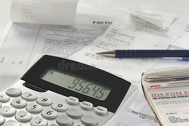 A calculator next to financial paperwork. stock image