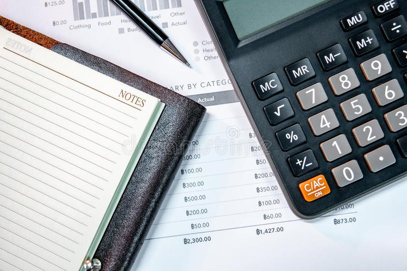 Calculator, notebook, pen and summary report paper stock photos