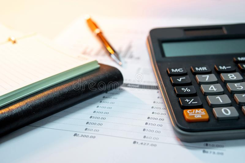 Calculator, notebook, pen and summary report paper stock photography