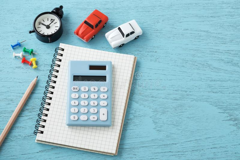 Calculator with toy car on wooden background. Calculator on notebook with toy car and clock on wooden table background stock images