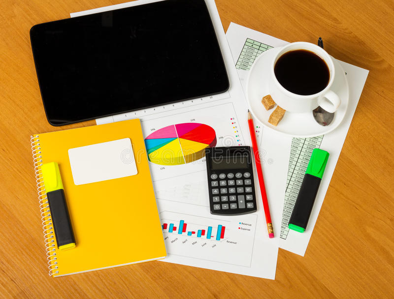 Calculator, notepad, business card, markers and cup coffee on worktable. Calculator, notepad, clean business card, pencil, markers and a cup of coffee on stock image