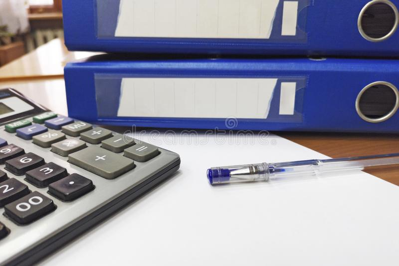 Calculator, office folder, pen and papers are waiting to be processed by businessan or bookkeeper. Internal Audit and tax concept stock photography