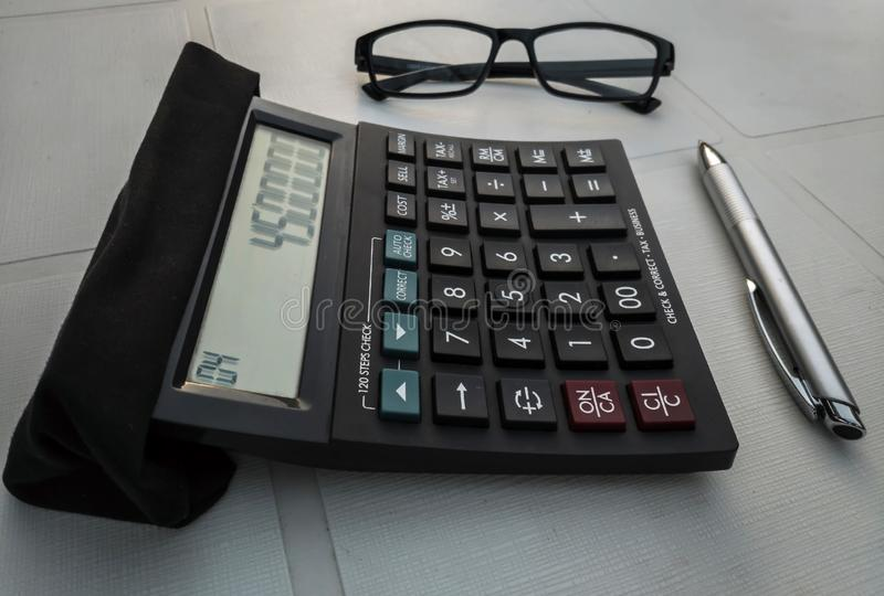 Calculator with a pair of glasses and a pen. On a table stock images