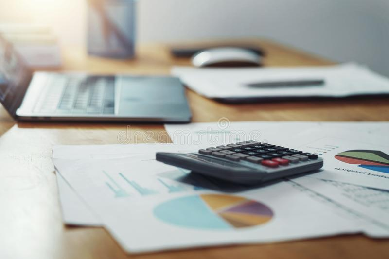calculator with paperwork and laptop on desk in office. concept finance and accounting stock images