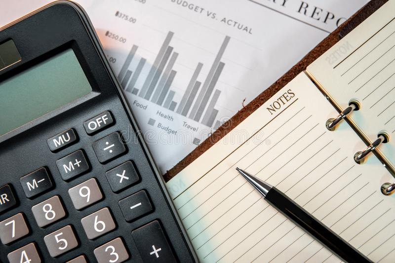 Calculator, notebook, pen and summary report paper royalty free stock image